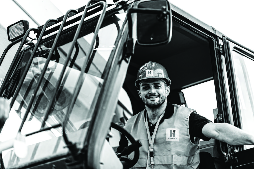Positive construction machine operator posing for camera. Black and white